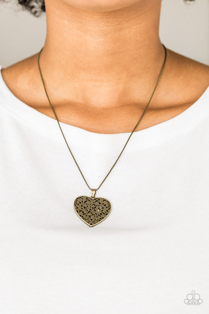 Filled with vine-like filigree detail, a brass heart pendant swings below the collar for a vintage inspired look. Features an adjustable clasp closure.  Sold as one individual necklace. Includes one pair of matching earrings.  Always nickel and lead free.