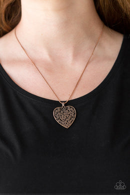Filled with vine-like filigree detail, a copper heart pendant swings below the collar for a vintage inspired look. Features an adjustable clasp closure.  Sold as one individual necklace. Includes one pair of matching earrings.  Always nickel and lead free.