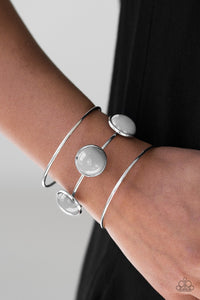 Three shimmery silver bars arc across the wrist, coalescing into an airy cuff. Three neutral gray beads are pressed into the center most bar for a bubbly finish.  Sold as one individual bracelet.  Always nickel and lead free.
