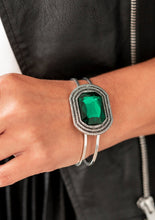 Load image into Gallery viewer, A dramatic emerald green gem is pressed into the center of textured silver frame, e.creating a glamorous centerpiece atop an airy silver cuff. Features a hinged closure.