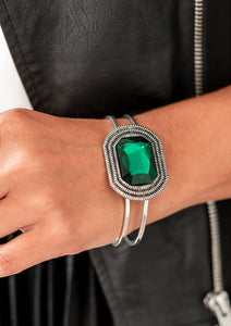 A dramatic emerald green gem is pressed into the center of textured silver frame, e.creating a glamorous centerpiece atop an airy silver cuff. Features a hinged closure.