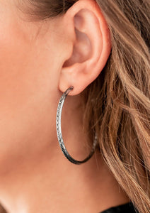 "A band of chiseled, gritty silver chain links is bordered by sleek silver bars and shaped into a hoop that curls boldly around the ear. Earring attaches to a standard post fitting. Hoop measure approximately 2"" in diameter."
