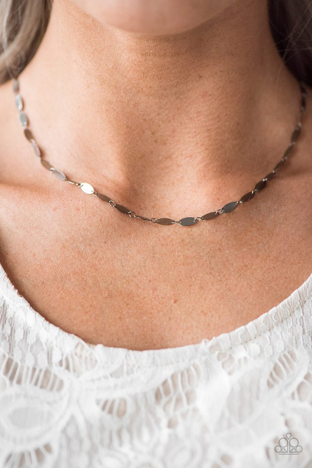 Flat gunmetal frames link together below the collar, creating a dainty chain. Brushed in a high-sheen finish, the flat gunmetal surfaces easily reflect the light creating a flashy palette from any angle. Features an adjustable clasp closure.  Sold as one individual necklace. Includes one pair of matching earrings.  Always nickel and lead free.