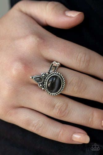 A teardrop and oval cat's eye stone is pressed into an ornate silver frame radiating with studded and metallic rope textures for a whimsical flair. Features a dainty stretchy band for a flexible fit.  Sold as one individual ring.  Always nickel and lead free.