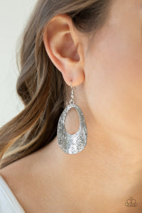 Rippling with tactile texture, an abstract silver teardrop swings from the ear for a casual look. Earring attaches to a standard fishhook fitting.  Sold as one pair of earrings.  Always nickel and lead free..