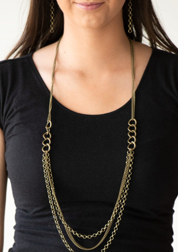 Bold brass chain links give way to layers of mismatched brass chain, creating a dramatic industrial collision. Features an adjustable clasp closure.  Sold as one individual necklace. Includes one pair of matching earrings.  Always nickel and lead free.