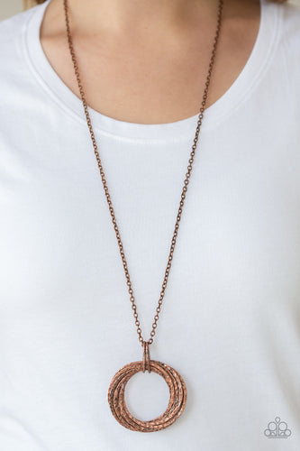 Featuring a hammered finish, a collection of interlocking copper hoops are threaded through the center of textured copper fittings. The dizzying pendant swings from the bottom of a lengthened copper chain for a dramatic industrial look. Features an adjustable clasp closure.  Sold as one individual necklace. Includes one pair of matching earrings.  Always nickel and lead free.