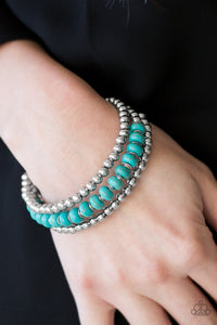 Sections of shiny silver beads and refreshing turquoise stones are threaded along a coiled wire, creating an earthy infinity wrap style bracelet.  Sold as one individual bracelet.  Always nickel and lead free.