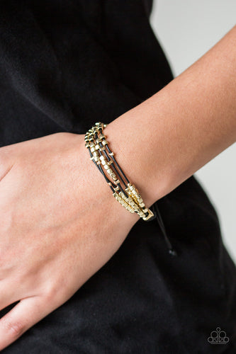 A collection of dainty gold beads and glistening gold cubes are threaded along strands of shiny black cording around the wrist for a minimalist inspired look. Features an adjustable sliding knot closure.  Sold as one individual bracelet.  Always nickel and lead free.