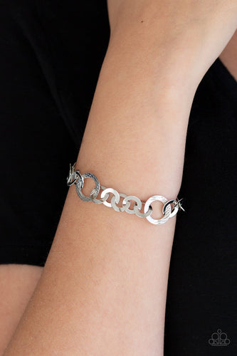 Smooth and textured silver hoops connect around the wrist for a modern industrial look. Features an adjustable clasp closure.  Sold as one individual bracelet.  Always nickel and lead free.