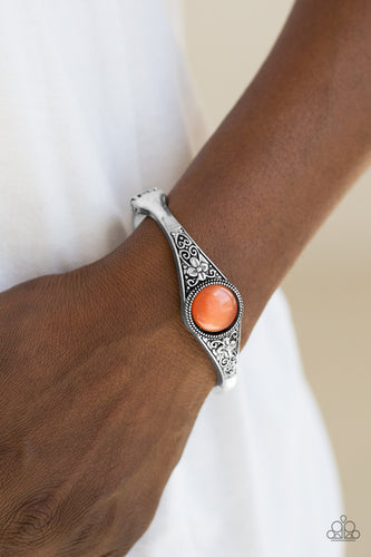 A glassy orange moonstone is pressed into the center of a shimmery silver bangle embossed in a whimsical floral pattern for a seasonal look. Features a hinged clasp.  Sold as one individual bracelet.  Always nickel and lead free.