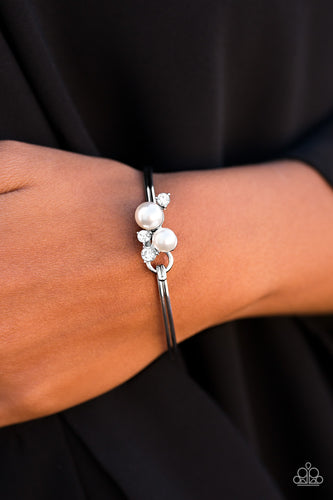A shimmery silver bar curls around the wrist, creating a dainty bangle. Pearly white beads join glittery white rhinestones, creating a clustered pendant atop the wrist for a refined look. Features a hinged clasp.  Sold as one individual bracelet. Always nickel and lead free.