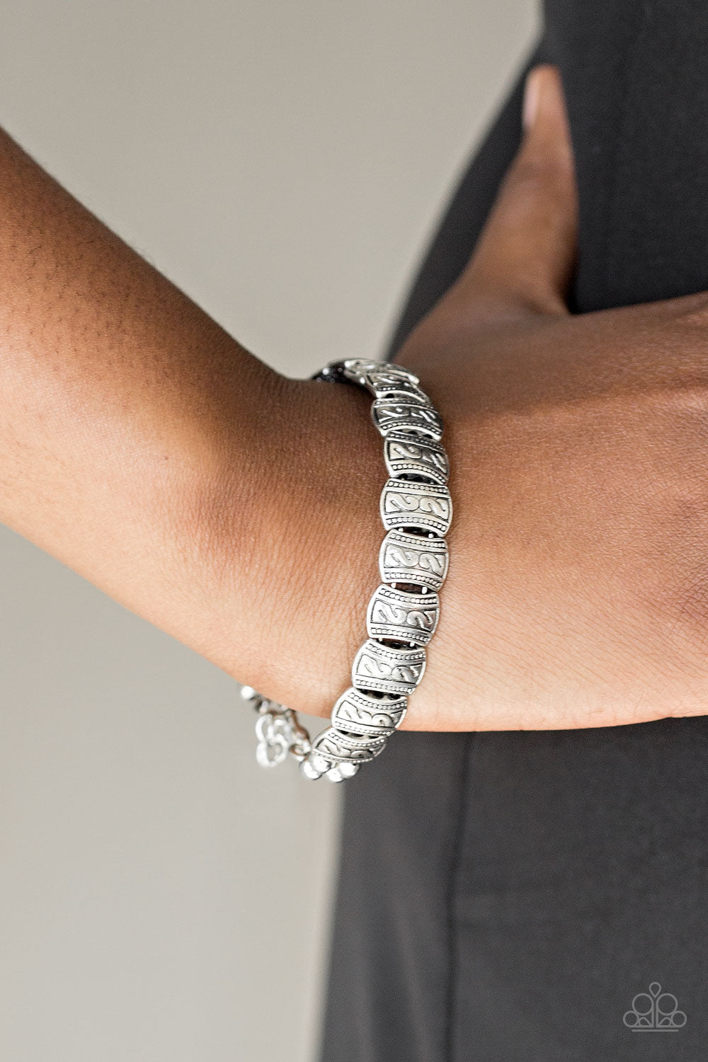 Embossed in tribal inspired patterns, dainty silver frames are threaded along a silver wire and wrapped around the wrist for a seasonal look. Features an adjustable clasp closure.  Sold as one individual bracelet.  Always nickel and lead free.