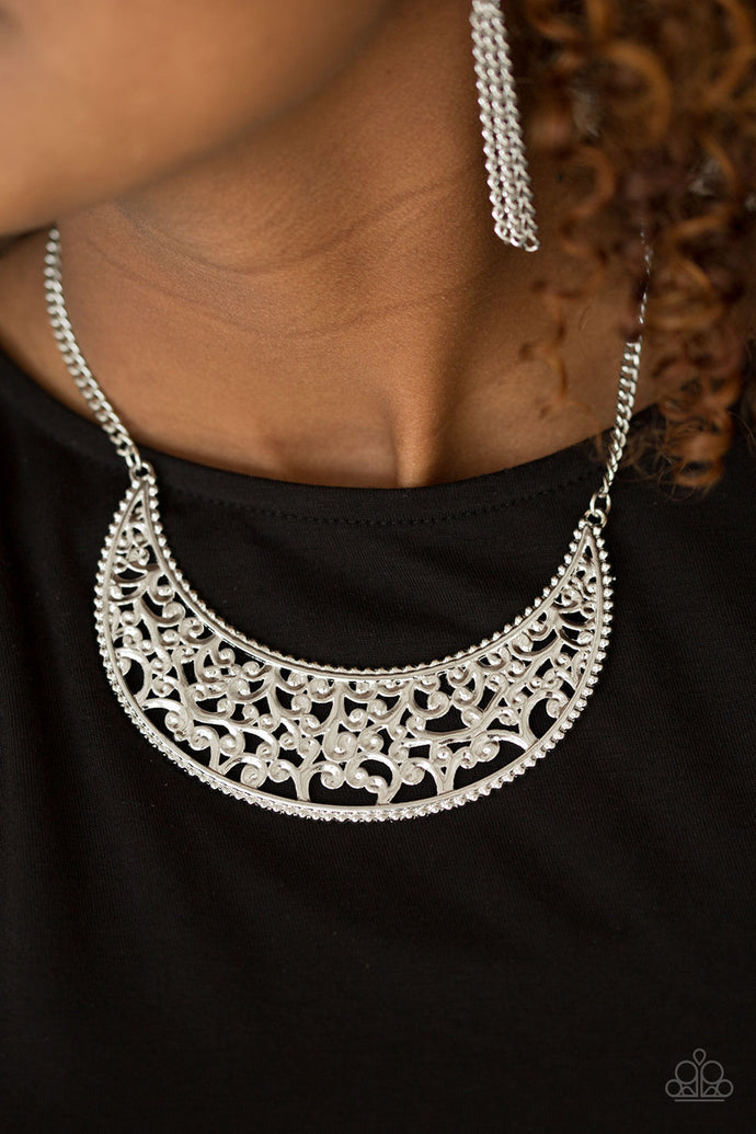 Silver vine-like filigree climbs a crescent shaped frame, creating a dramatic pendant below the collar. Features an adjustable clasp closure.  Sold as one individual necklace. Includes one pair of matching earrings.  Always nickel and lead free.