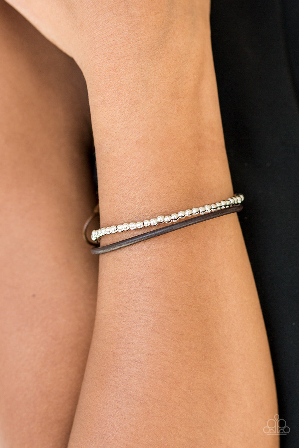A strand of glistening silver beads and a strand of shiny brown leather cording wrap around the wrist, creating dainty layers. Features an adjustable sliding knot closure.  Sold as one individual bracelet.  Always nickel and lead free.