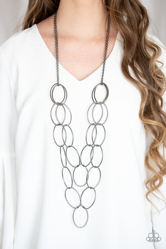 Etched in antiqued textures, pairs of over sized gunmetal ovals link across the chest for a bold industrial look. Features an adjustable clasp closure.  Sold as one individual necklace. Includes one pair of matching earrings.  Always nickel and lead free.