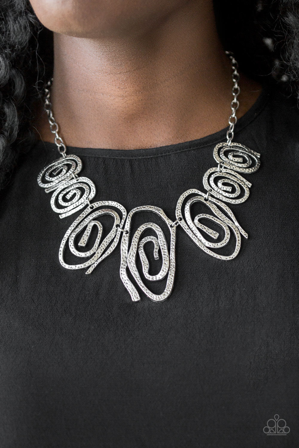 Delicately hammered in shimmery detail, warped silver frames spin into dizzying spirals. Gradually increasing in size near the center, the asymmetrical frames link below the collar for a bold tribal inspired look. Features an adjustable clasp closure.  Sold as one individual necklace. Includes one pair of matching earrings.  Always nickel and lead free.