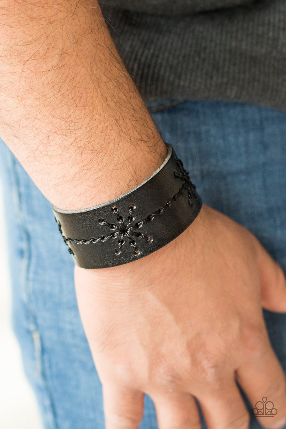 Shiny black thread is stitched across the front of a black leather band, creating a nautical inspired pattern. Features an adjustable snap closure.  Sold as one individual bracelet.   Always nickel and lead free.