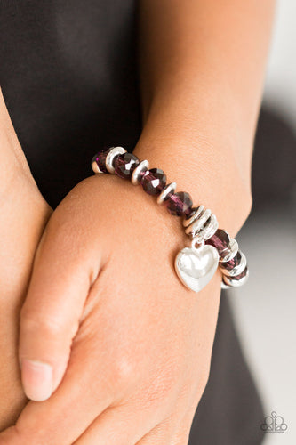 Sparkling purple crystal-like beads and shimmery silver accents are threaded along a stretchy band. An over-sized silver heart charm swings from the wrist for a whimsical finish.  Sold as one individual bracelet. Always nickel and lead free.