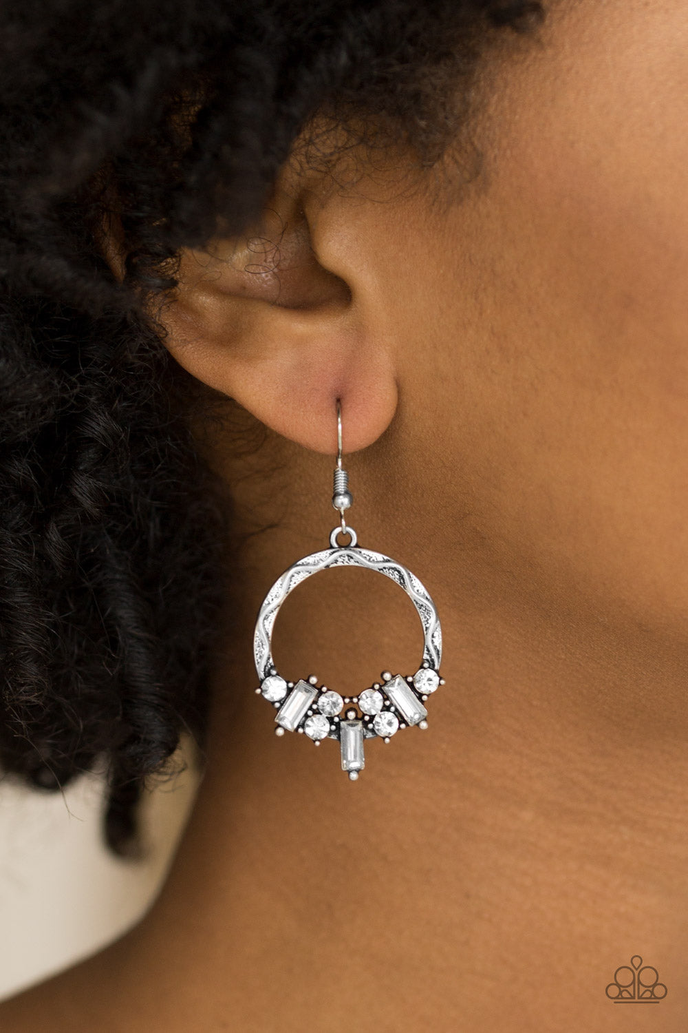 Featuring round and emerald style cuts, radiant white rhinestones are encrusted along the bottom of an ornate silver hoop for an edgy look. Earring attaches to a standard fishhook fitting.  Sold as one pair of earrings.  Always nickel and lead free.