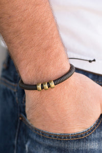 Shiny black twine wraps around a black cord, creating an urban look around the wrist. Shiny brass beads slide along the cording for a rugged finish. Features an adjustable sliding knot closure.  Sold as one individual bracelet.  Always nickel and lead free.