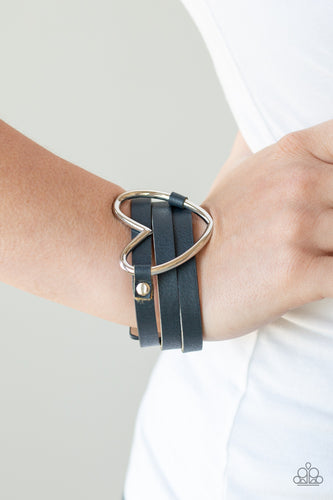 An over sized silver heart frame is studded in place across the center of a spliced blue leather band for a seasonal look. Features an adjustable snap closure.  Sold as one individual bracelet.   Always nickel and lead free.