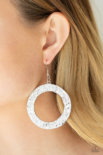 Brushed in a rustic silver finish, a flat circular frame has been hammered in blinding detail for a handcrafted look. Earring attaches to a standard fishhook fitting.  Sold as one pair of earrings.  Always nickel and lead free.