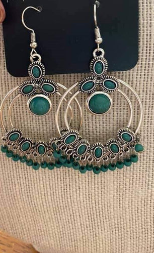 Polished green beading swings from the bottom of a frilly silver frame, creating a whimsical fringe. Earring attaches to a standard fishhook fitting. earrings.  Sold as one pair of earrings.  Always nickel and lead free.
