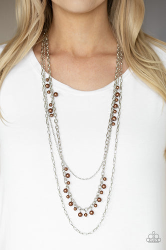 Three mismatched silver chains layer down the chest. Dainty brown pearls cascade down one silver chain, adding a flirty twist to the timeless pearl palette. Features an adjustable clasp closure.  Sold as one individual necklace. Includes one pair of matching earrings.  Always nickel and lead free.
