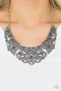Featuring lattice-like patterns, shimmery silver flowers bloom below the collar for a seasonal look. Features an adjustable clasp closure.  Sold as one individual necklace. Includes one pair of matching earrings.  Always nickel and lead free.