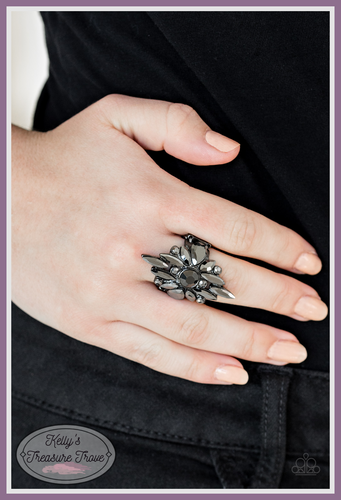 Varying in shape and size, a collision of glittery hematite rhinestones burst across the finger, coalescing into a blinding frame. Features a stretchy band for a flexible fit.  Sold as one individual ring.  By Paparazzi Accessories. Always nickel and lead free.