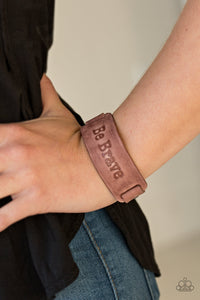 "Brushed in a rustic finish, a brown leather band is stamped in the phrase, ""Be Brave"" for an inspiring finish. Features an adjustable snap closure.  Sold as one individual bracelet.  Always nickel and lead free."
