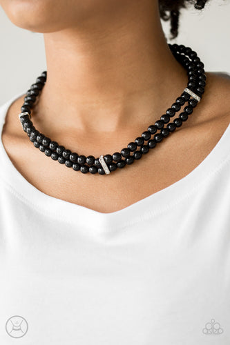 Pinched between white rhinestone encrusted frames, strands of classic black beads layer around the neck for a timeless look. Features an adjustable clasp closure.  Sold as one individual necklace. Includes one pair of matching earrings.  Always nickel and lead free.
