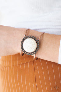 A refreshing white stone is pressed into the center of a shimmery copper frame radiating with sunburst details. The earthy frame sits atop an airy copper cuff for a seasonal finish.