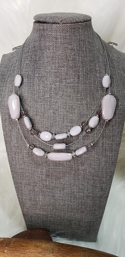 Infused with dainty metallic accents, a collection of silver gray and sparkling crystal-like beads are threaded along invisible wires below the collar for a whimsically layered look. Features an adjustable clasp closure.  Sold as one individual necklace. Includes one pair of matching earrings.  Always nickel and lead free.  Fashion Fix Exclusive April 2020