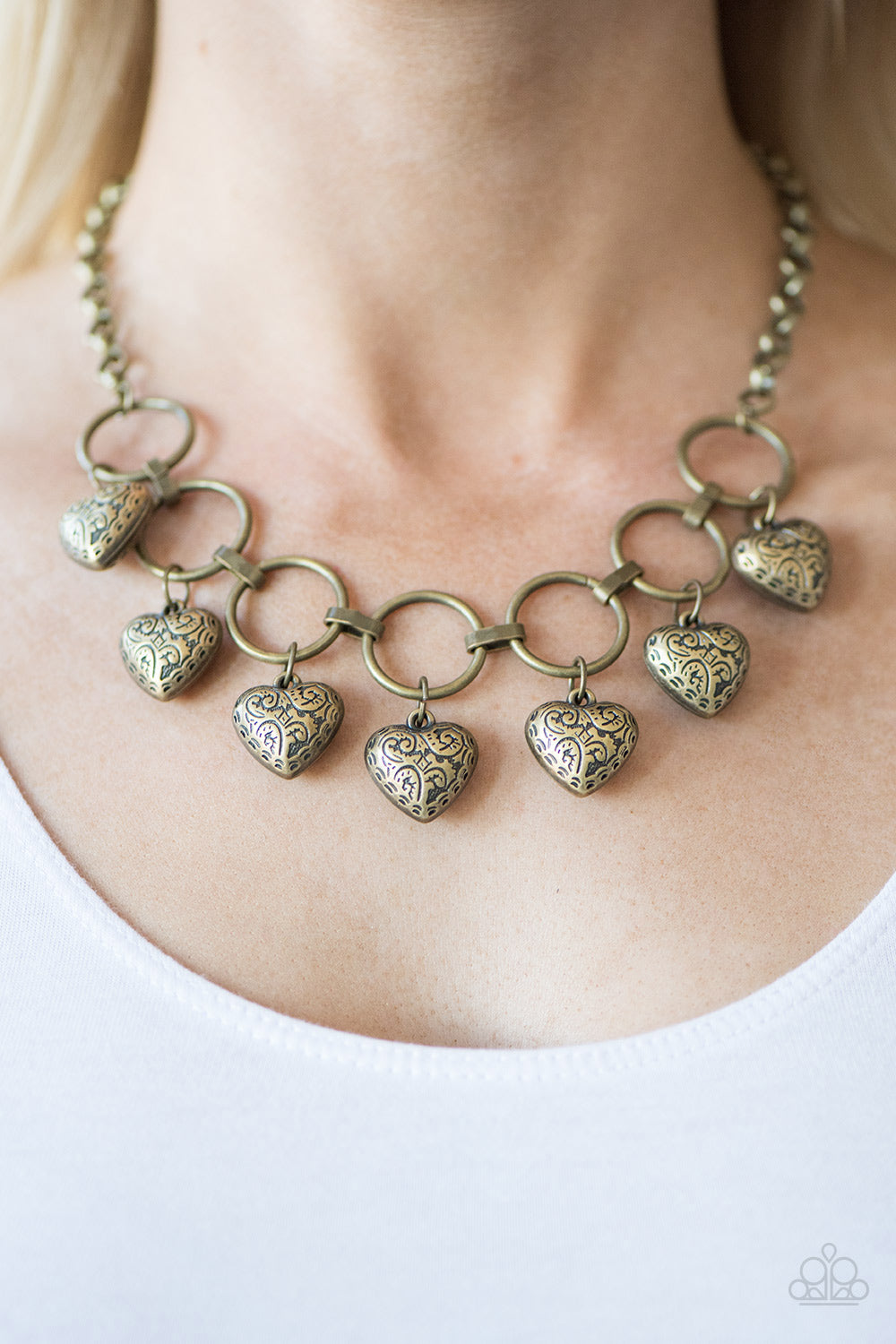 Stamped in whimsical patterns, vintage inspired hearts cascade from the bottom of airy brass hoops, creating a romantic fringe below the collar. Features an adjustable clasp closure.  Sold as one individual necklace. Includes one pair of matching earrings. Always nickel and lead free.