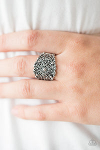Brushed in an antiqued shimmer, silver filigree climbs the finger, swirling into a rustic floral frame. Features a stretchy band for a flexible fit.  Sold as one individual ring.   Always nickel and lead free.