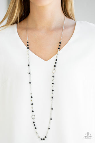 A collection of shiny black beads, twisting silver hoops, and faceted silver beads trickle along an asymmetrical silver chain for a refined look. Features an adjustable clasp closure.  Sold as one individual necklace. Includes one pair of matching earrings. Always nickel and lead free.