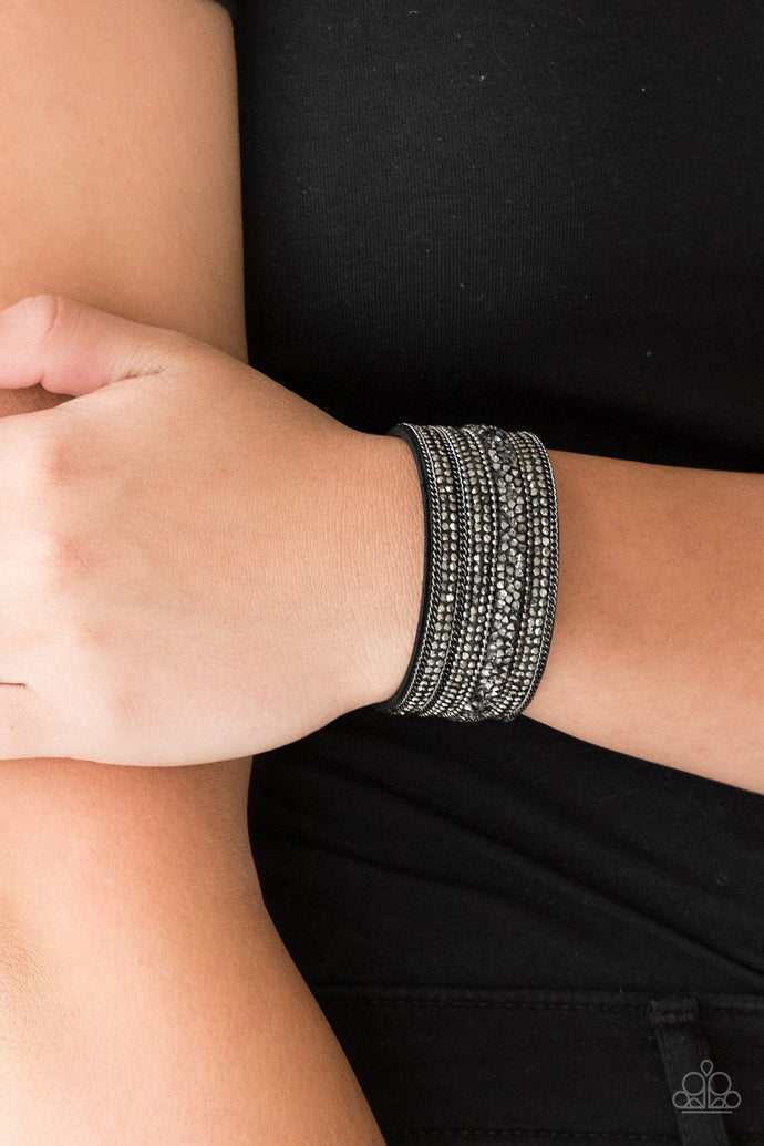 Rows of shimmery gunmetal chains, glittery hematite rhinestones, and metallic prism rhinestones are sprinkled along a thick black suede band for a sassy style. Features an adjustable snap closure.  Sold as one individual bracelet.  Always nickel and lead free.
