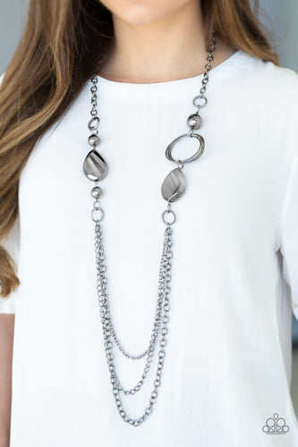A mismatched collection of oversized gunmetal beads, hoops, and textured gunmetal accents give way to layers of gunmetal chains down the chest for an edgy industrial look. Features an adjustable clasp closure.  Sold as one individual necklace. Includes one pair of matching earrings.   Always nickel and lead free.