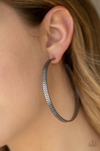 Stamped in dizzying textures, a glistening gunmetal bar curls into an oversized hoop for a retro look. Earring attaches to a standard post fitting. Hoop measures approximately 2 3/4