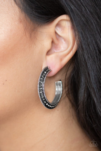 The top half of a bold silver frame is encrusted in hematite rhinestones, giving way to glistening silver studs for an edgy finish. Earring attaches to a standard post fitting. Hoop measures approximately 1 1/4