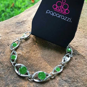 Green rhinestones are sprinkled along silver marquise-shaped frames, creating a glitzy chain around the wrist. Dazzling white rhinestones embellish two of the larger silver frames, adding a hint of refined shimmer to the rich palette.  Features an adjustable clasp closure.  Always nickel and lead free.