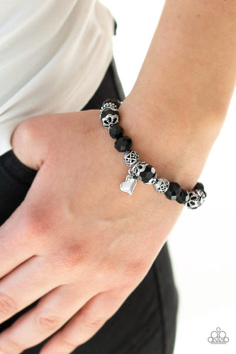 A collection of black crystal-like beads and ornate silver beads are threaded along a stretchy band around the wrist. An abstract silver heart charm swings from the center, for a romantic finish.  Sold as one individual bracelet. Always nickel and lead free.