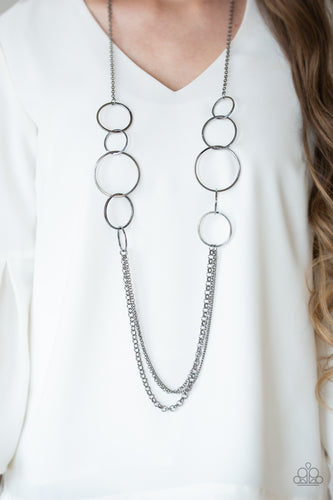 A collection of interlocking gunmetal rings give way to layers of mismatched gunmetal chains down the chest, creating a stunning tone-on-tone statement piece. Features an adjustable clasp closure.  Sold as one individual necklace. Includes one pair of matching earrings.  Always nickel and lead free.