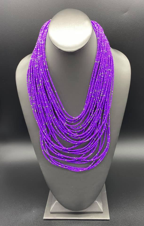 Suspended between two gunmetal fittings, row after row of countless strands of purple seed beads layer below the collar. Dainty gunmetal seed beads are sprinkled across the strands for a seasonal finish. Features an adjustable clasp closure.  Sold as one individual necklace. Includes one pair of matching earrings.  Always nickel and lead free!  Fashion Fix Exclusive July 2020