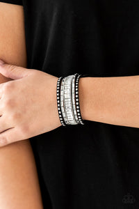 Shiny silver studs, dainty silver ball chains, and edgy white emerald-cut rhinestones race along a spliced black suede band for a rock star look. Features an adjustable snap closure.  Sold as one individual bracelet. Always nickel and lead free.