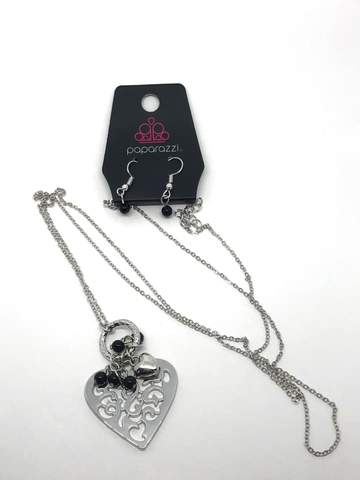 Infused with dainty black pearls and a shimmery silver heart charm, a stenciled silver heart pendant swings from the bottom of a lengthened silver chain for a whimsical look. Features an adjustable clasp closure.  Sold as one individual necklace. Includes one pair of matching earrings.  Always nickel and lead free.