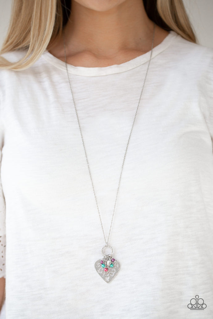 Infused with dainty multicolored pearls and a shimmery silver heart charm, a stenciled silver heart pendant swings from the bottom of a lengthened silver chain for a whimsical look. Features an adjustable clasp closure.  Sold as one individual necklace. Includes one pair of matching earrings.  Always nickel and lead free.