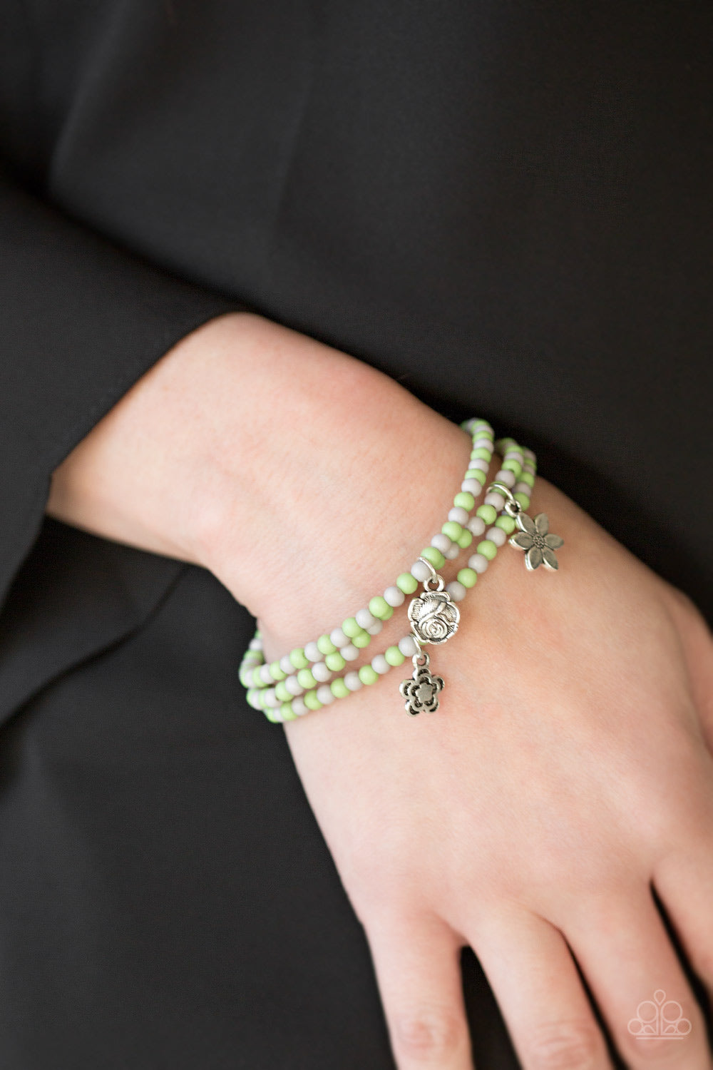 Dainty green and gray beads are threaded along stretchy elastic bands, creating colorful layers across the wrist. Brushed in an antiqued shimmer, dainty floral charms swing from the wrist for a seasonal finish.  Sold as one set of three bracelets.  Always nickel and lead free.